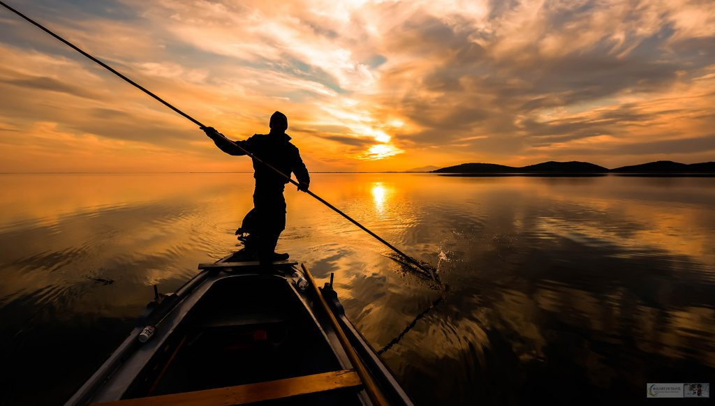 Fisherman on Messolonghi Lagoon in Greece at sunset