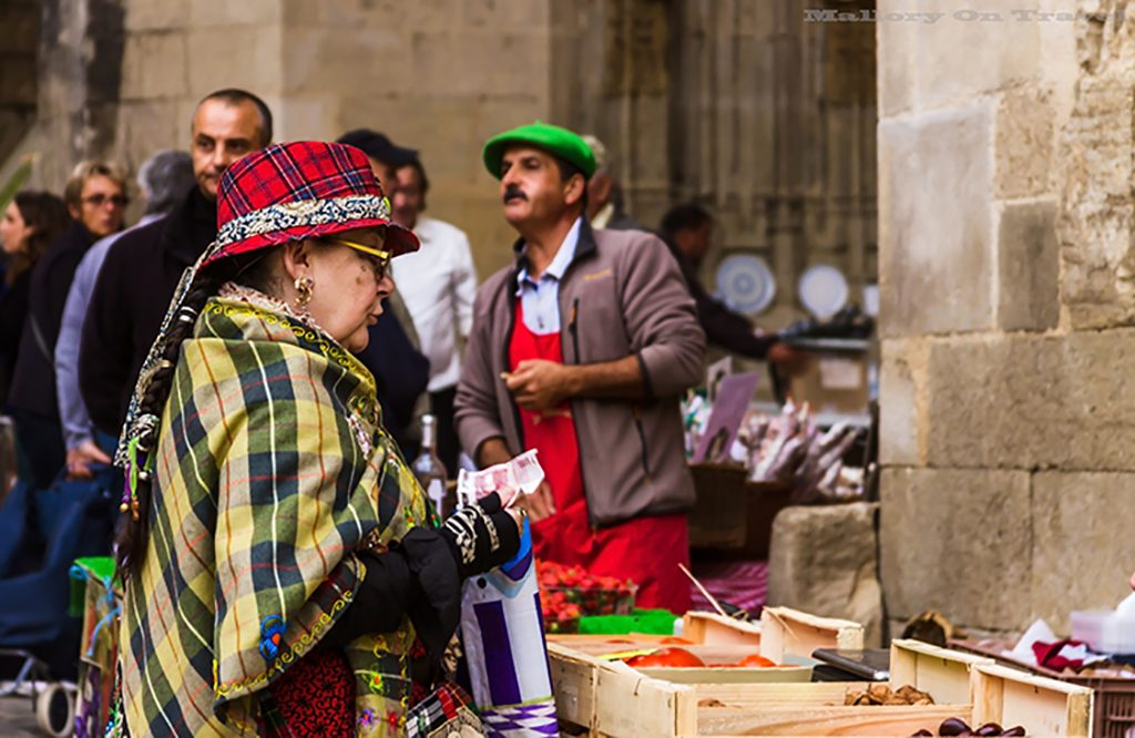 Shopper at the markets of Villefrance-de-Rouergue in Place Notre Dame in the Aveyron region of France on Mallory on Travel adventure, adventure travel, photography Iain_Mallory_Ave1403196 villefrance_de_rouergue